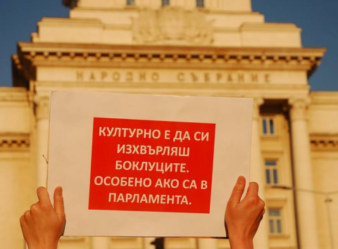 "A protester holding a sign in front of the Parliament Building. The sign reads ""It's polite to throw out your garbage. Especially if it's in Parliament."""